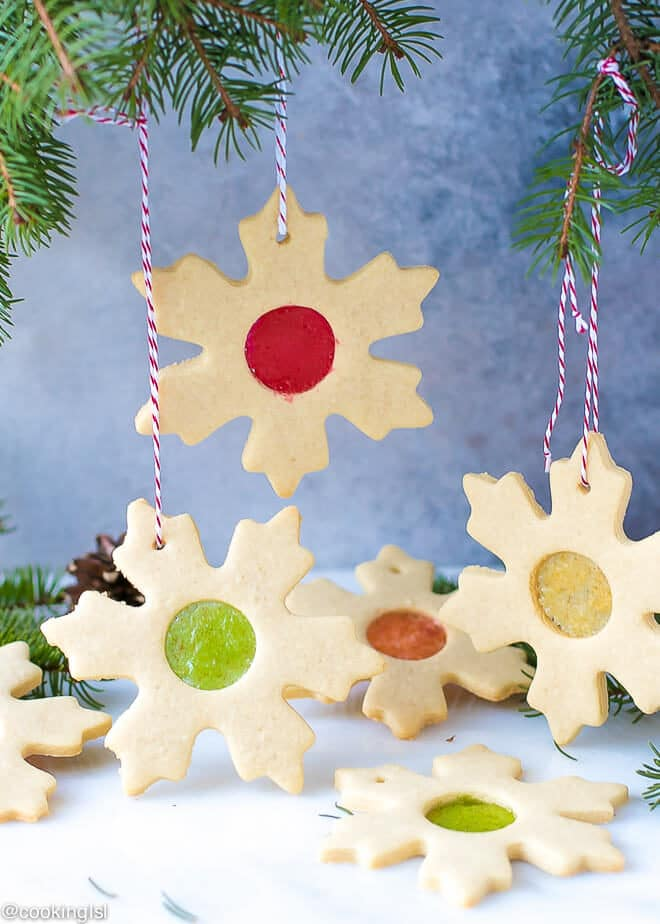 Easy Stained Glass Cookies Recipe- gorgeous cookie stars with candy glass effect in the middle, hanging on a Christmas tree.