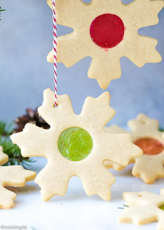 Easy Stained Glass Cookies Recipe- gorgeous cookie stars with candy glass effect in the middle, hanging with barker's twine in red and white, with Christmas greens and pine cones.