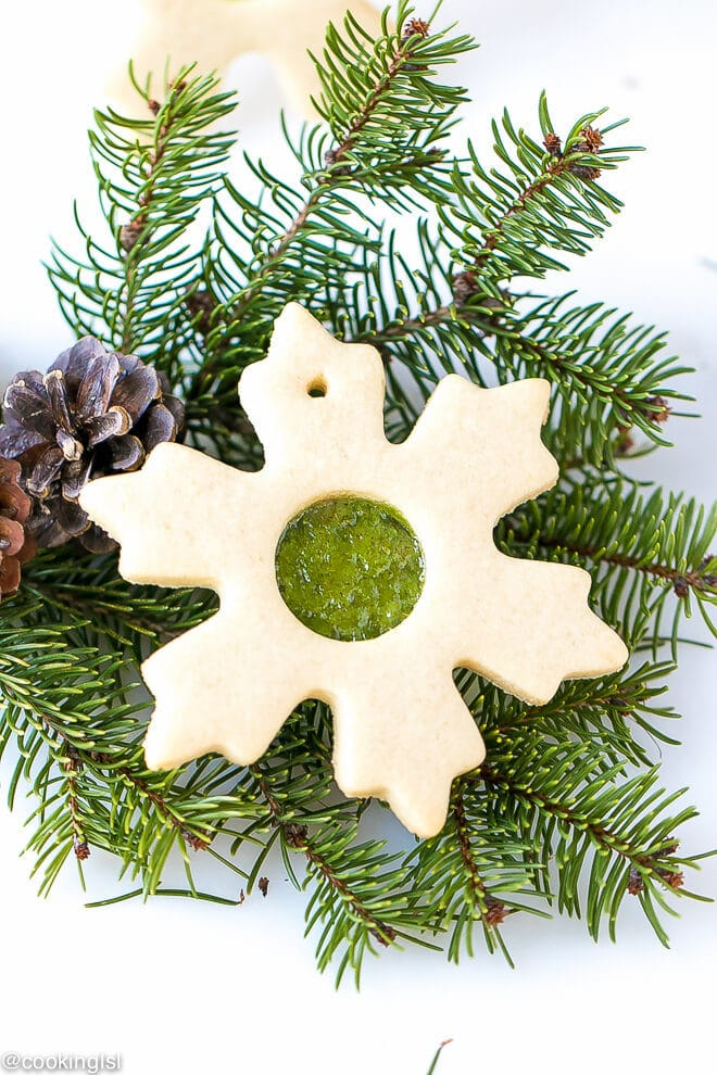 Easy Stained Glass Cookies Recipe - buttery sugar cookies, cut out in the shape of snowflake, with a clear candy window. Placed on Christmas tree branch.With pinecones on the side.