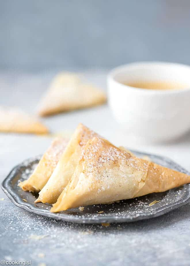 Pumpkin Phyllo Triangles Recipe on a metal plate, dusted with powdered sugar and cinnamon.