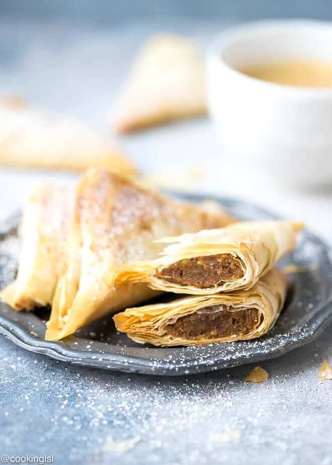 Pumpkin Phyllo Triangles Recipe . A phyllo triangle cut through the middle, filling shown, topped with powdered sugar.