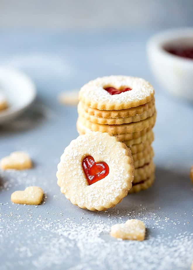 Easy Almond Linzer Cookies Recipe. Round cutout cookies, with heart cutouts on the top cookies, sandwiched together with freezer jam.