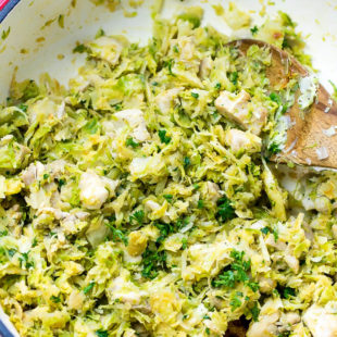 One Pot Chicken Thighs With Brussels Sprouts Recipe .A white pan (braiser) filled with sauteed Brussels Sprouts and chicken.