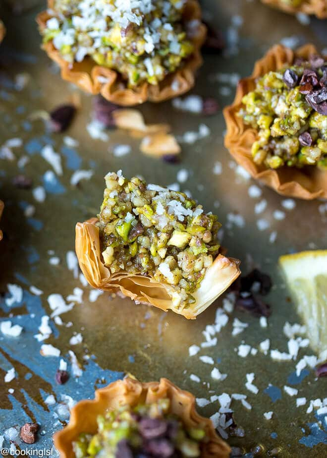 Mini Baklava phyllo cups recipe- on a serving tray, a bite taken into it, golden brown.