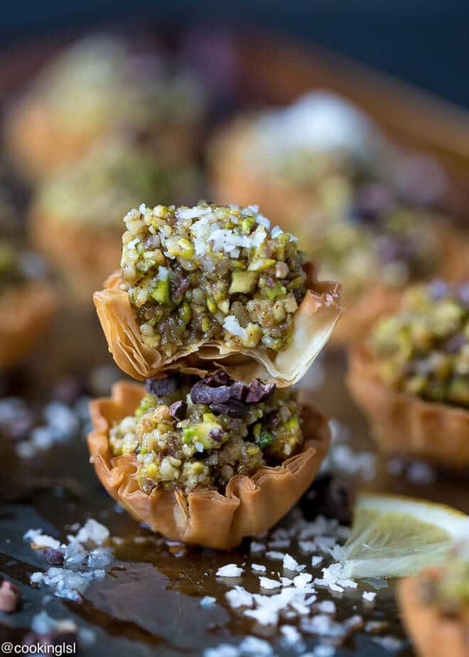 Party dessert. A tray with mini phyllo baklava cups, colorful and flakey, topped with coconut flakes.