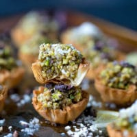 A tray with mini phyllo baklava cups, colorful and flakey, topped with coconut flakes.
