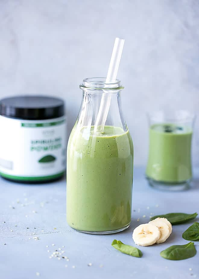 Spirulina Smoothie Recipe in a tall clear glass container, with a clear straw and a box of Spriulina powder on the side.