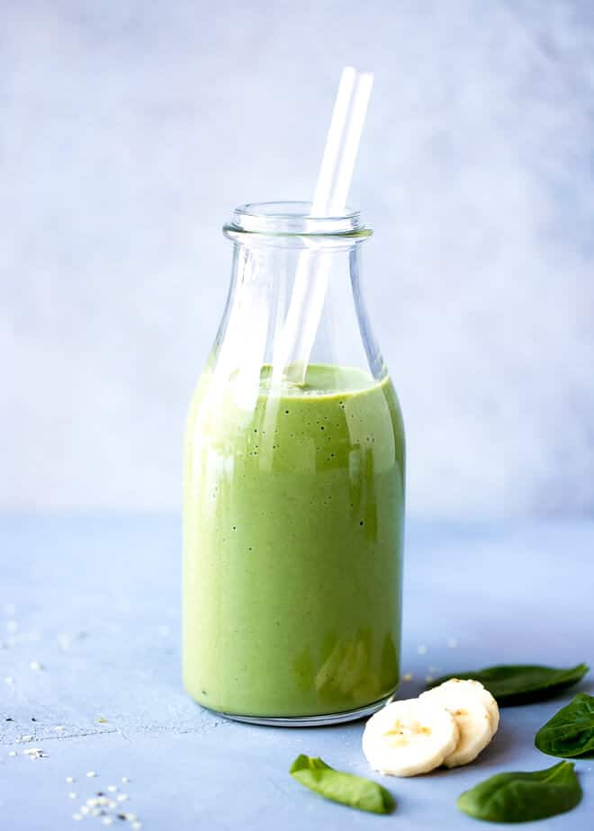 Spirulina Smoothie Recipe garnished with banana slices and baby spinach.