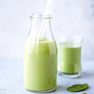 Spirulina Smoothie Recipe in a tall clear glass, with spinach and hemp seeds on the side.