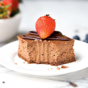 Chocolate Cheesecake Bars Recipe- a square slice of chocolate cheesecake, drizzled with ganache, topped with strawberry