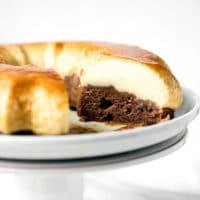 Easy Chocoflan Recipe - Kodrit Kadir. Creme caramel flan in a bundt pan, inverted over a white platter on a cake stand.