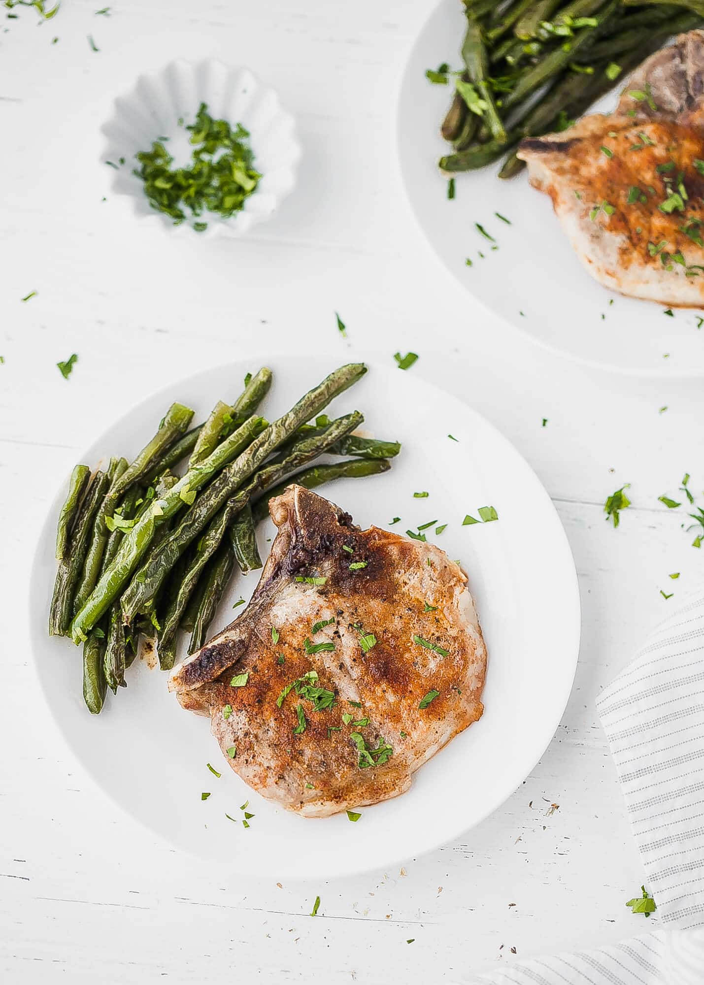 Oven Baked Bone-In Pork Chops Recipe - juicy, tender pork chops, seasoned with flavorful four ingredient dry rub and quickly baked in the oven to perfection. A quick, simple and effortless weeknight meal for busy people. These baked pork chops are served with a side of baked green beans, but any vegetable of your choice can be added instead of green beans.