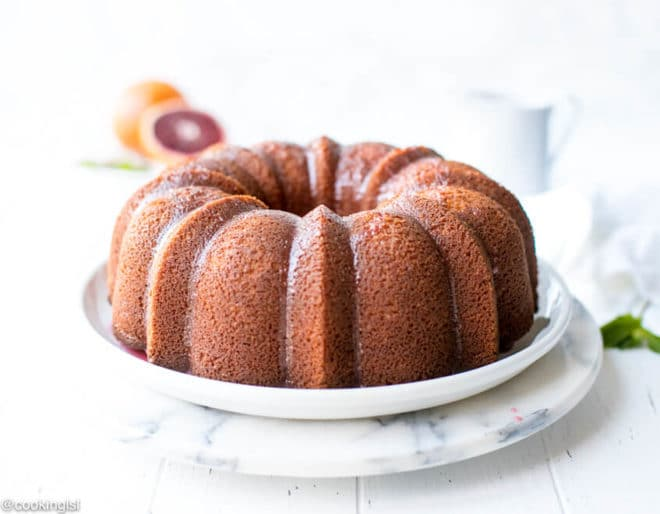 Easy Blood Orange Bundt Cake Recipe-moist and tender orange pound cake on a white plate, with fresh blood orange and flavorful, simple blood orange glaze.