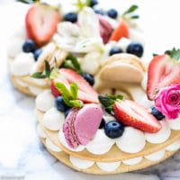 Cream Tart Recipe - New Cake Trend on a platter, topped with macarons, strawberries, flowers, meringue cookies, berries.