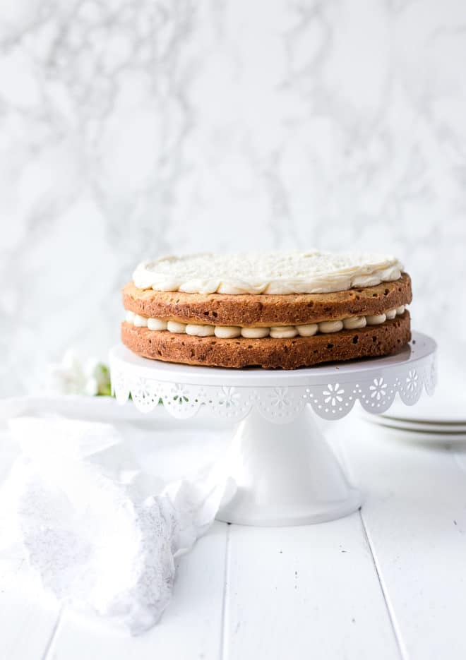 Naked keto carrot cake on a white cake pedestal