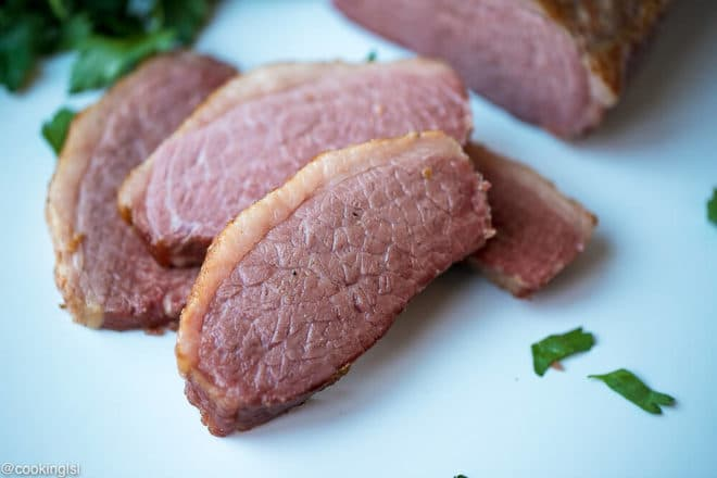Slow Cooker Corned Beef Recipe, tender, juicy meat with spices on top on cutting board.