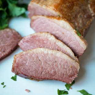 Slow Cooker Corned Beef Recipe, sliced on a cutting board, pink on the inside and crispy on the outside.