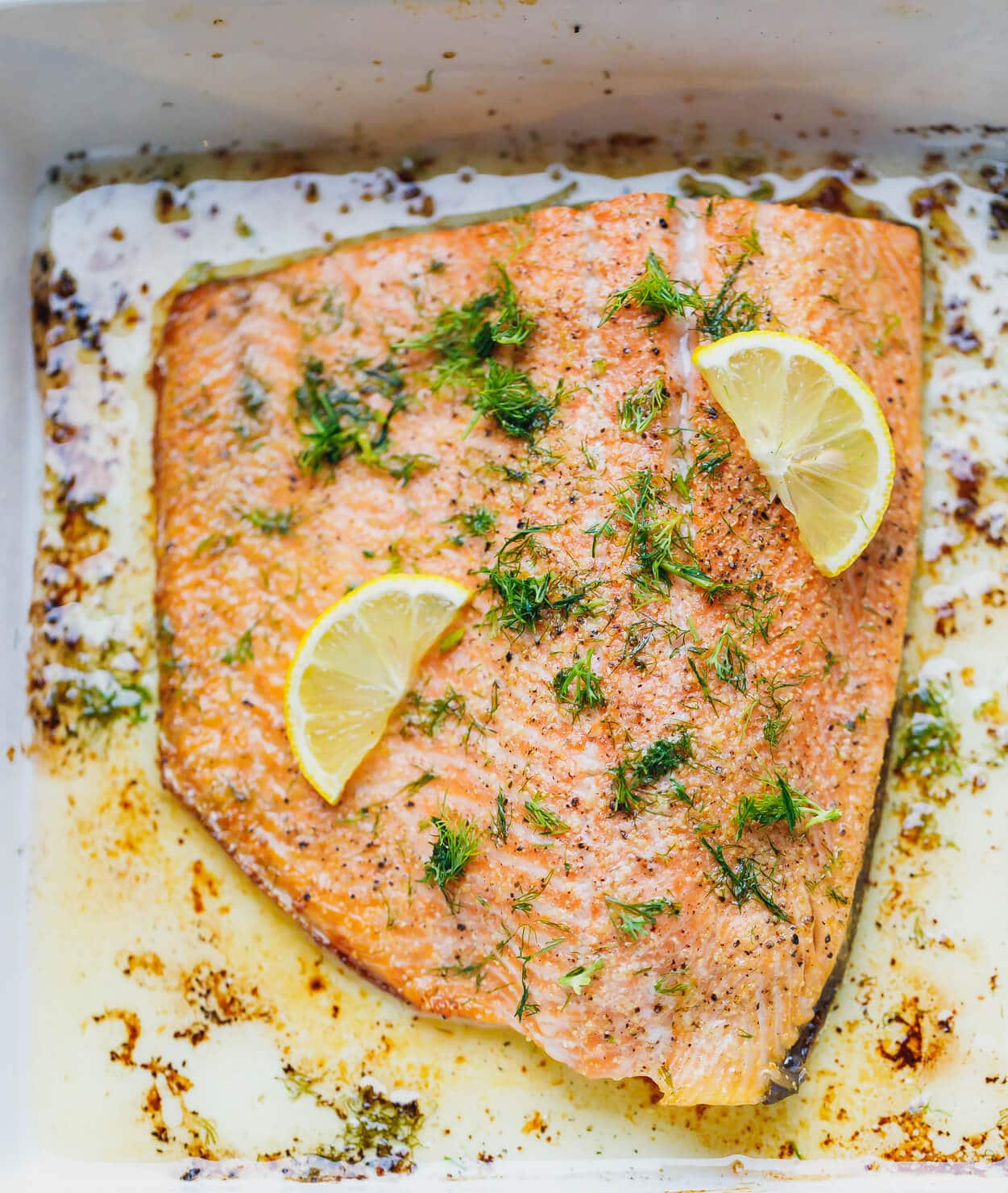 Easy One Pan Garlic Dill Lemon Baked Salmon Recipe - ready in under 30 minutes, simple and delicious sheet pan dinner that could be paired with a salad or roasted veggies for the perfect effortless nutritious meal. All you need are seven staple ingredients. #bakedsalmon #salmonrecipes #salmondinner #ketodinner #garlicsalmon