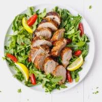 Grilled pork tenderloin, sliced on a platter with salad