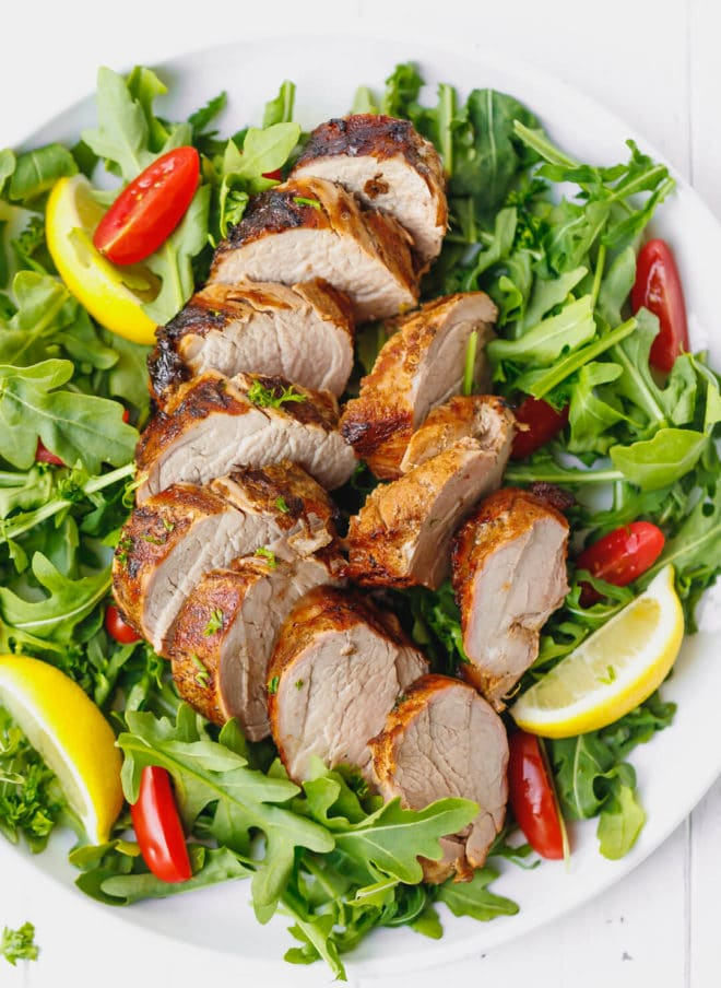 grilled pork tenderloin, juicy, sliced on a plate