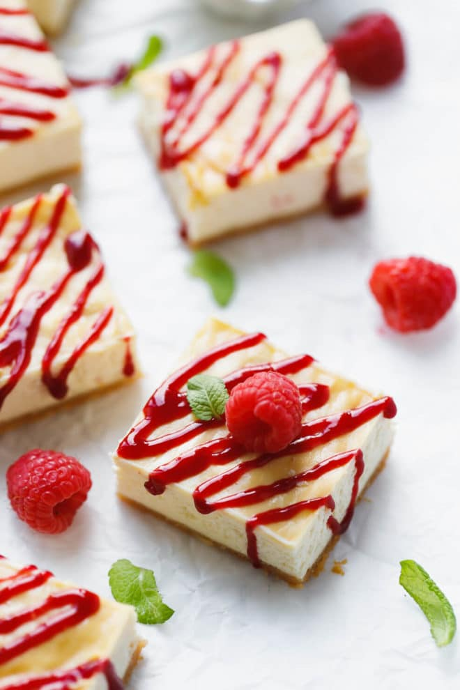 Raspberry Cheesecake Bars on parchment paper