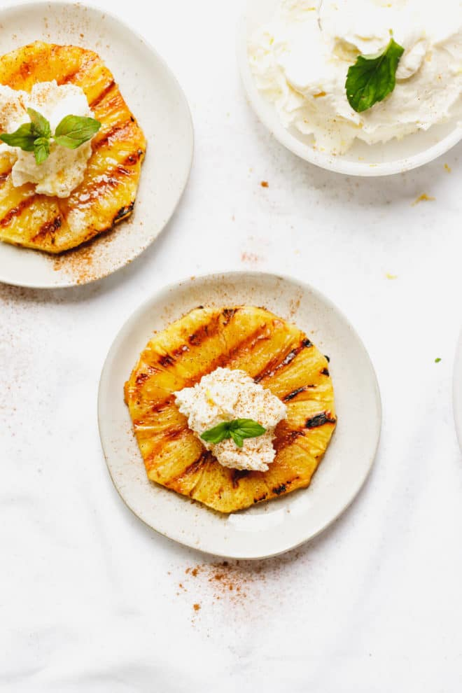 Two plates with rounds of grilled pineapple and a bowl of mascarpone whipped cream