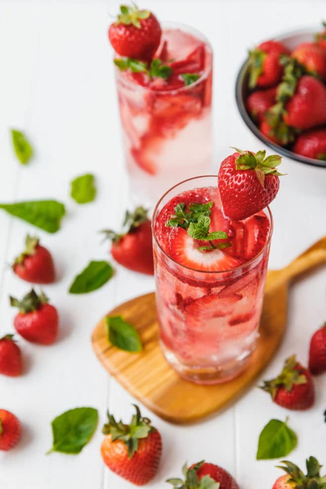 Sugar-Free Strawberry Smash Cocktail in a tall glass on a wooden board