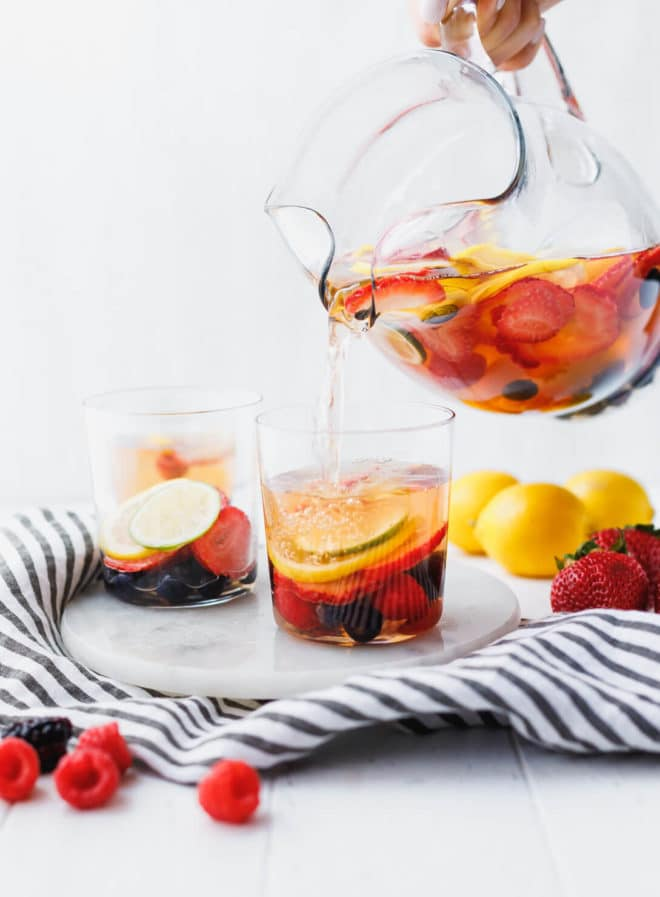 White wine berry sangria in a pitcher pouring into a glass