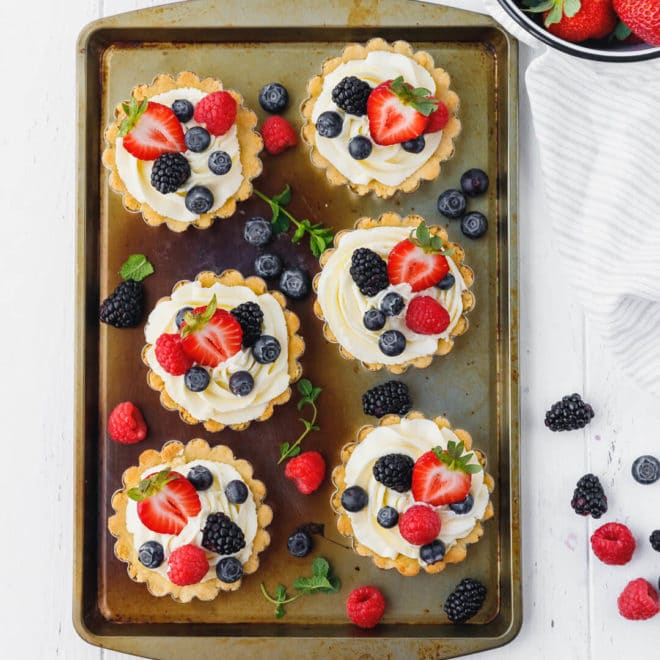 Low-Carb, Keto Tarts With Berries And Mascarpone Cream in tins on a baking cookie sheet