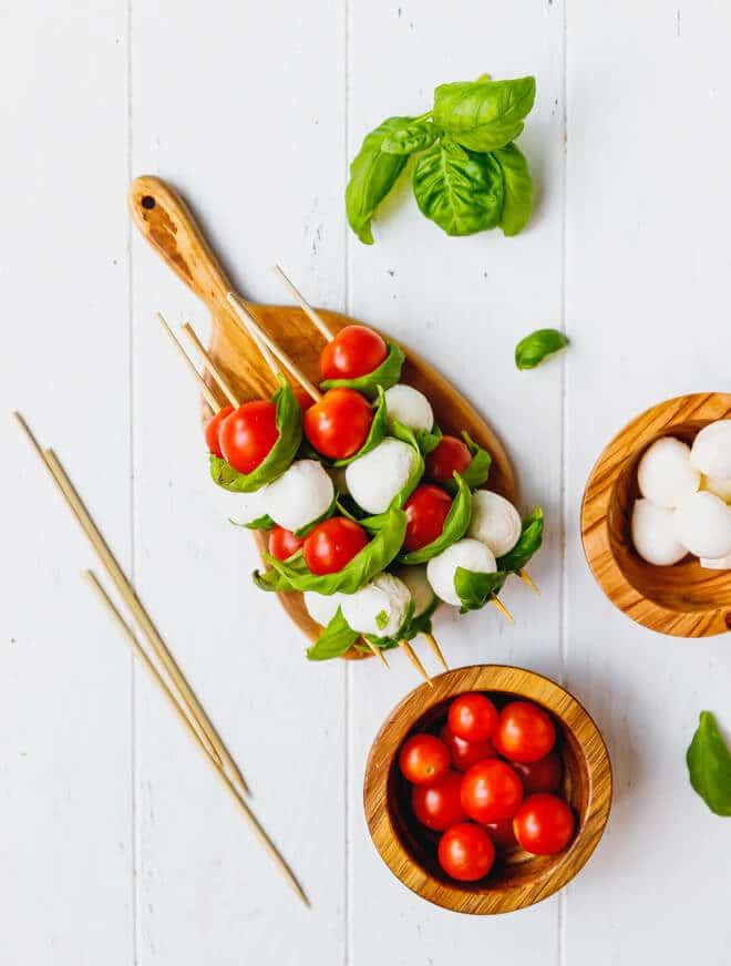 Caprese Skewers With Balsamic on a platter with tomatoes on the side
