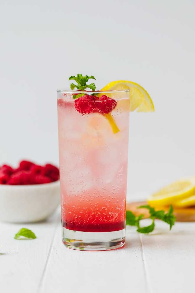 Raspberry lemonade in tall glass with lemon slice
