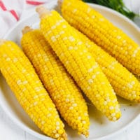 Ears or boiled corn on the cob on a white plate