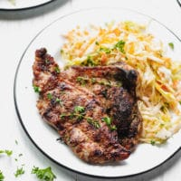 How To Cook Pork Shoulder Steak recipe- steak on a plate with cabbage salad