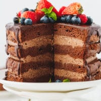 Keto chocolate cake on a cake stand with slices cut out