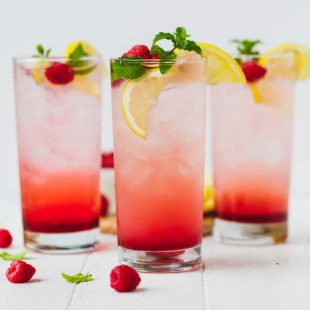 raspberry lemonade in three clear tall glasses