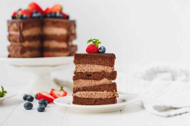 A slice of Keto chocolate cake and a cake on a stand