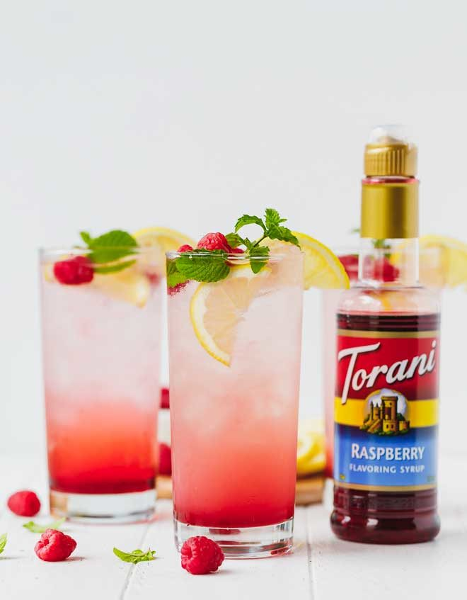 Sparkling raspberry lemonade in tall clear glasses with a bottle of torani syrup next to them