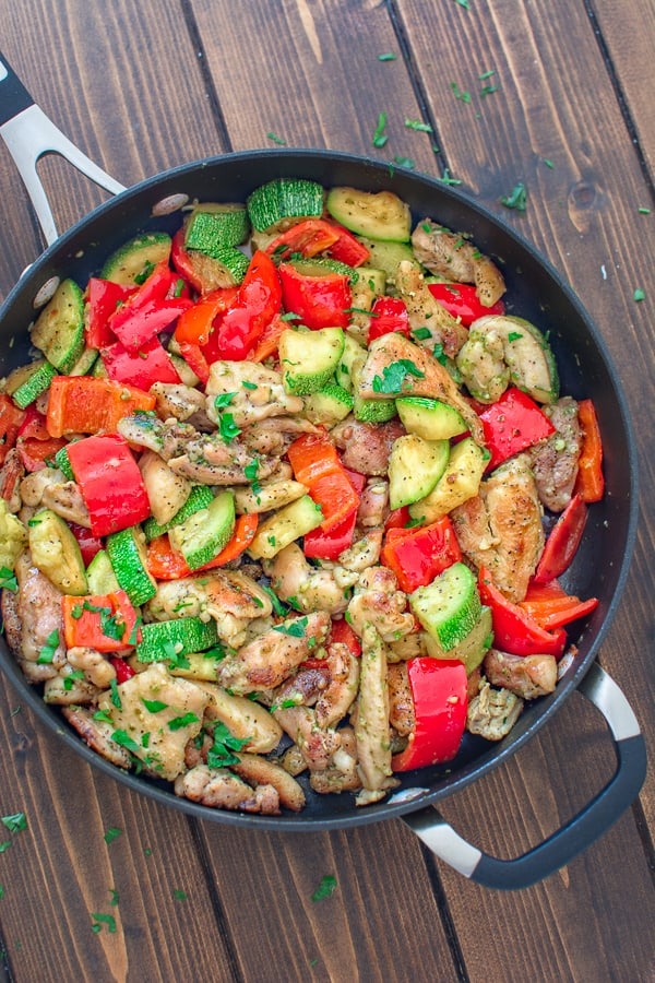 Pesto chicken thighs and veggies in a skillet