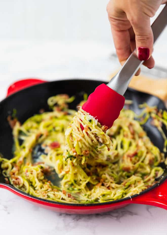 Low-carb zucchini carbonara in a pan with thongs grabbing the pasta