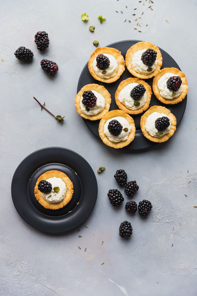 Low-Carb Lavender Blackberry Tarts on black platters