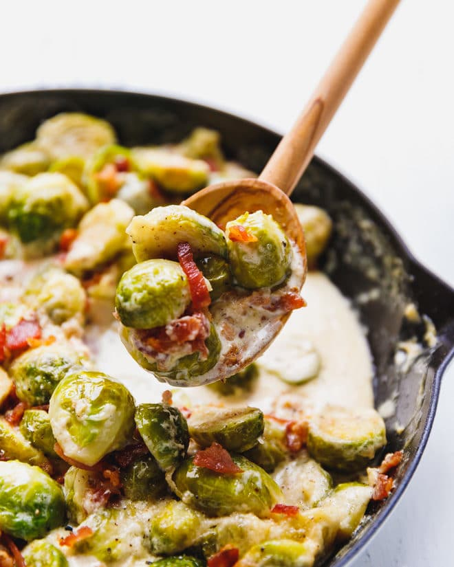 Cheesy Creamy Brussel Sprouts With Bacon in a wooden spoon