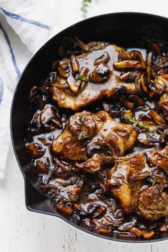 Pork steak with mushrooms and onions in a pan