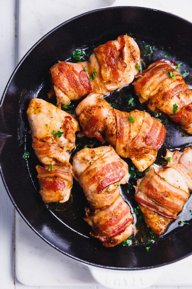 Boneless skinless chicken thighs wrapped in bacon in a pan