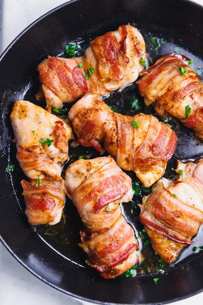 Bacon wrapped chicken thighs in a pan