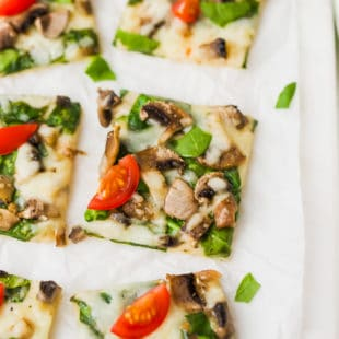 Easy Cauliflower Pizza With Spinach And Mushrooms on a cutting board
