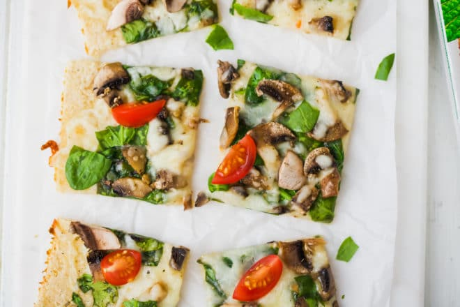 Easy Cauliflower Pizza With Spinach And Mushrooms on a platter