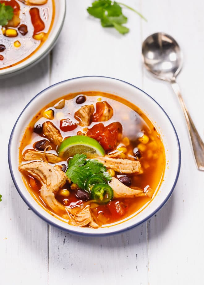 Easy homemade chicken tortilla soup in white bowl with blue rim