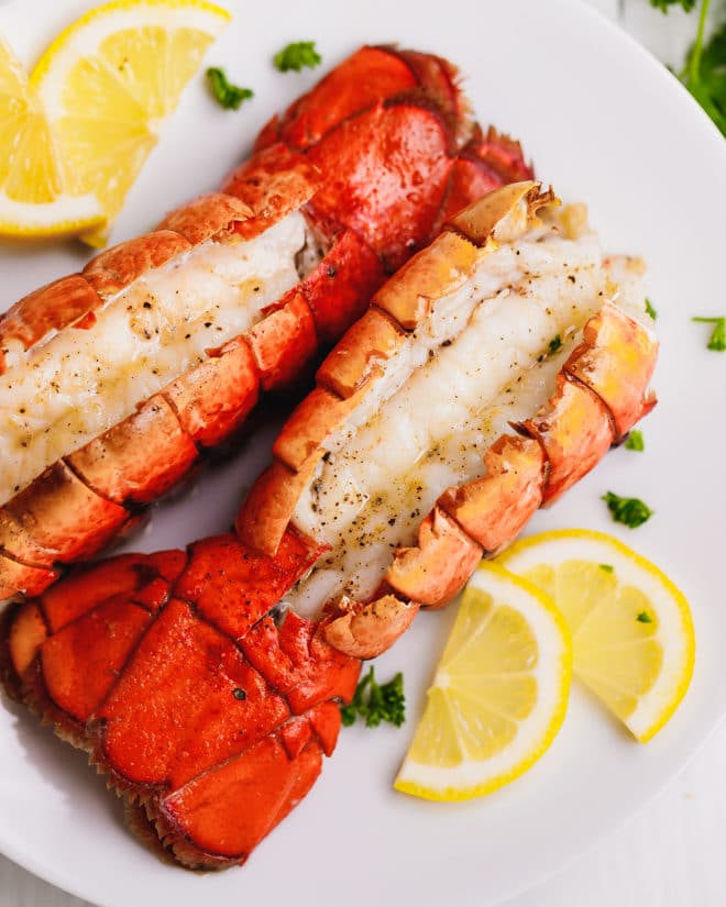 Two broiled lobster tails on a plate