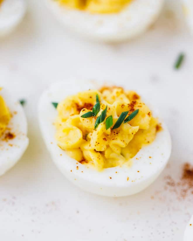 Deviled egg on a white plate with paprika on top