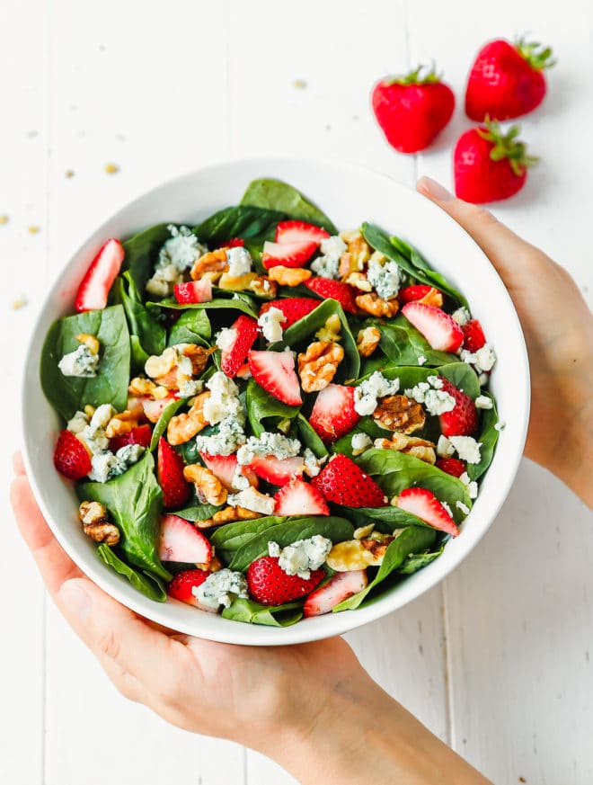 Hands holding a bowl of strawberry spinach salad